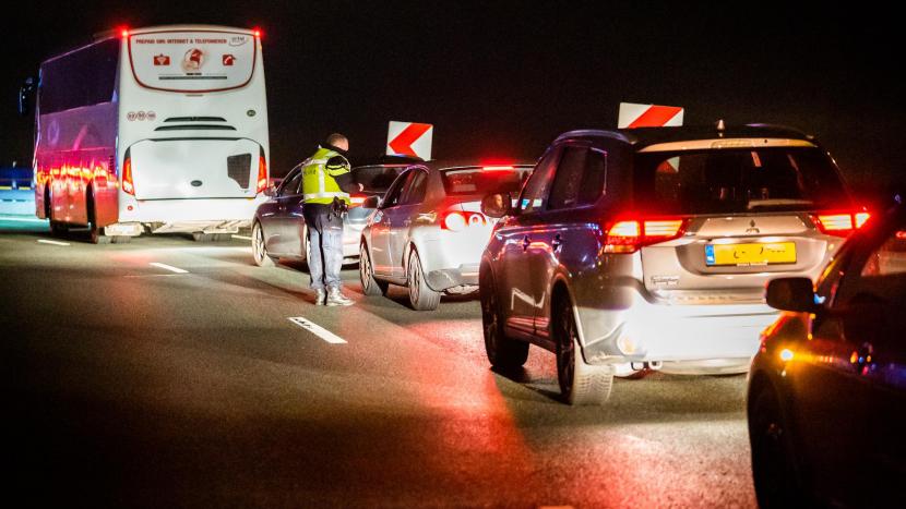 Een agent bekeurt automobilisten die een rood kruis negeerden